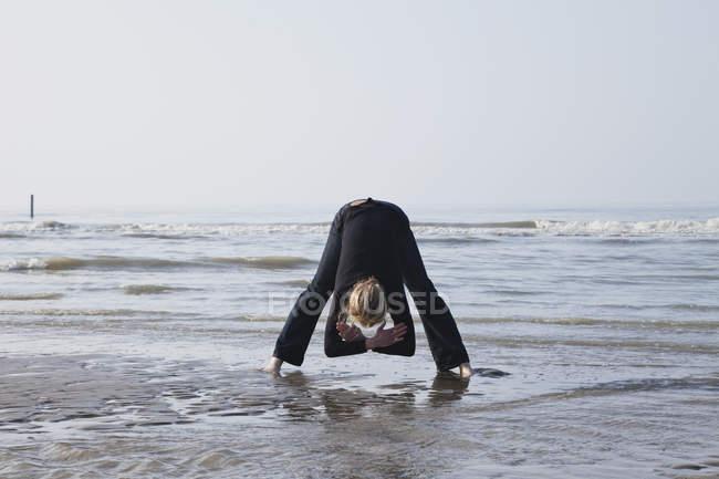 Bélgica, Mujer joven haciendo ejercicio en el Mar del Norte - foto de stock