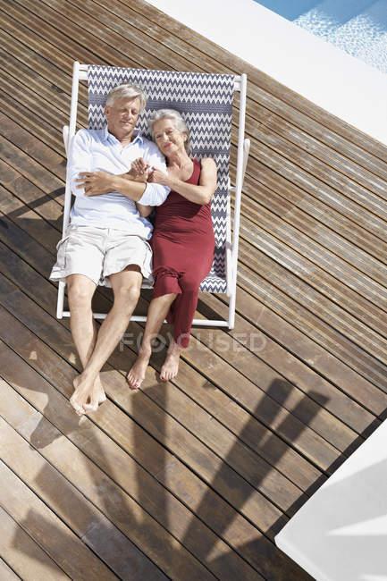 Старшая пара отдыхает на шезлонгах на пляже — стоковое фото