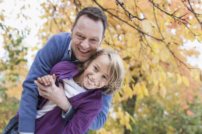 Отец и сын обнимаются в осеннем саду — стоковое фото