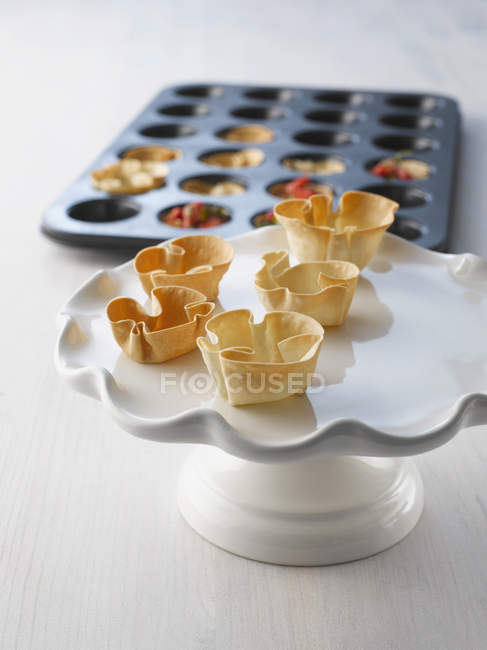 Baked dough baskets on cakestand, baking tray in background, close up — Stock Photo