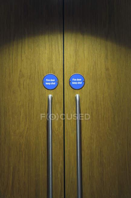 Geschlossener Tür mit Zeichen und Griffe, full-frame — Stockfoto