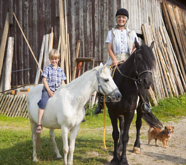 Mature woman and boy on horse — Stock Photo