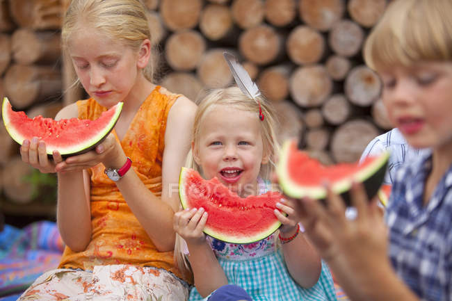 Group of children eating watermelon at garden — Stock Photo