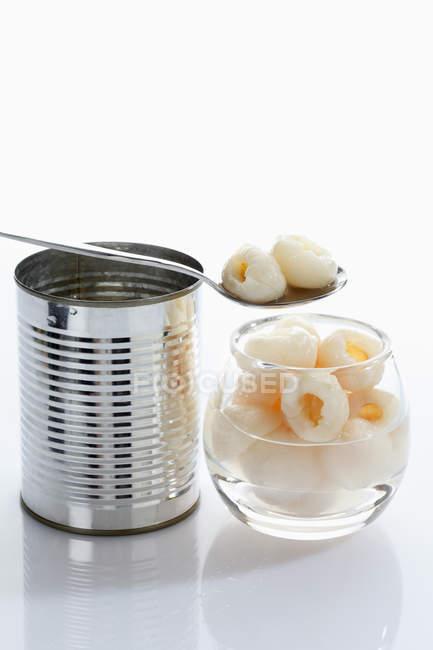 Litchi in ciotola di vetro con latta su priorità bassa bianca — Foto stock
