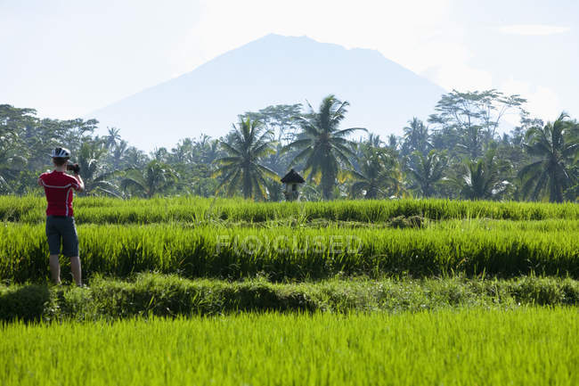 Indonesia, Bali, Man standing in field taking photograph, Mount Agung in background — Stock Photo