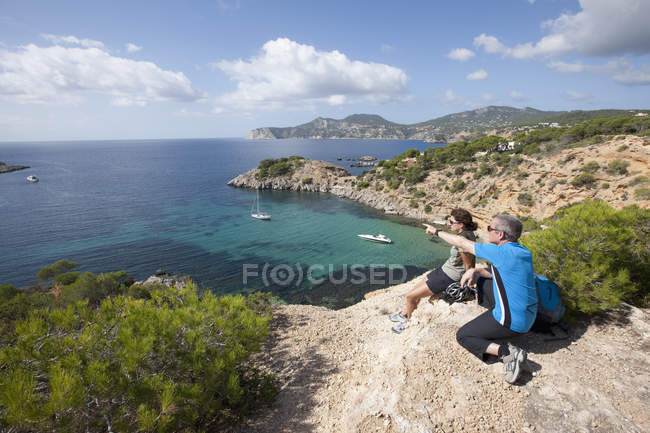Spain, Ibiza, Porroig, Mature man and mid adult woman looking at view — Stock Photo