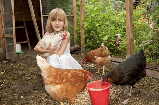 Mädchen spielt mit Hühnern im Hühnerstall — Stockfoto