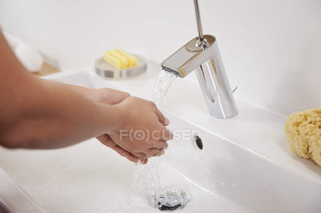 Young woman washing hands in bathroom sink — Stock Photo