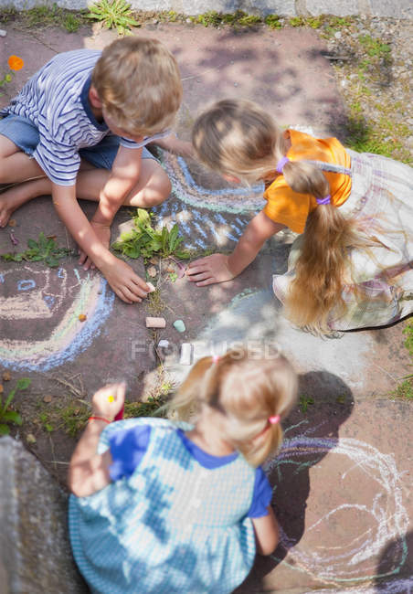 Group of children drawing on walkway with chalk — Stock Photo