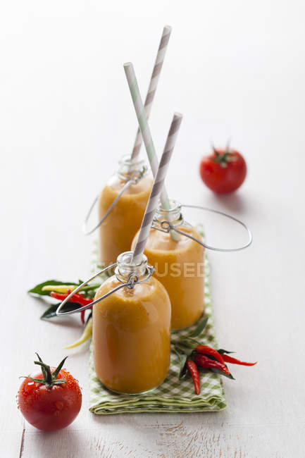 Bottles of gazpacho with chillies and tomatoes on napkin — Stock Photo