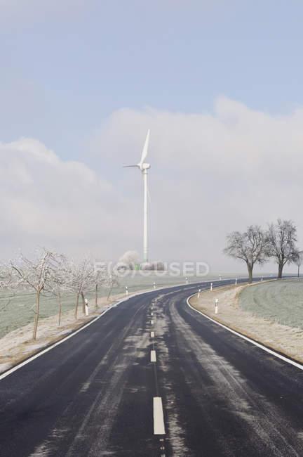 Дорога с ветряной турбиной — стоковое фото