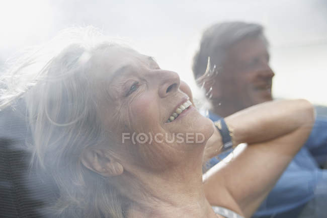 Senior couple in convertible car, smiling — Stock Photo