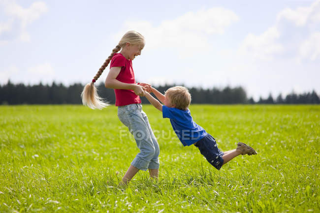 Boy and girl playing in meadow — Stock Photo