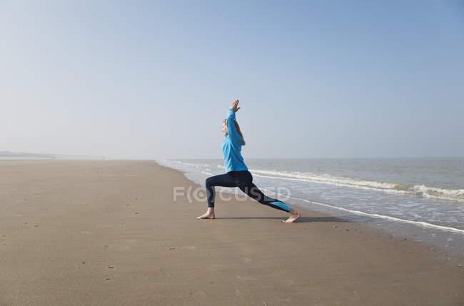 Bélgica, Mujer madura haciendo ejercicio en el Mar del Norte - foto de stock