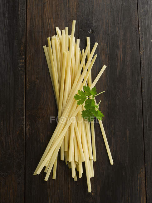 Uncooked tagliatelle on wood table, close up — Stock Photo