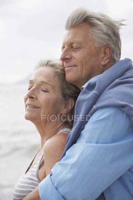 Senior couple on beach at Atlantic ocean, smiling — Stock Photo