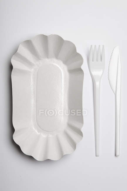 Disposable plate with plastic fork and knife on white background — Stock Photo
