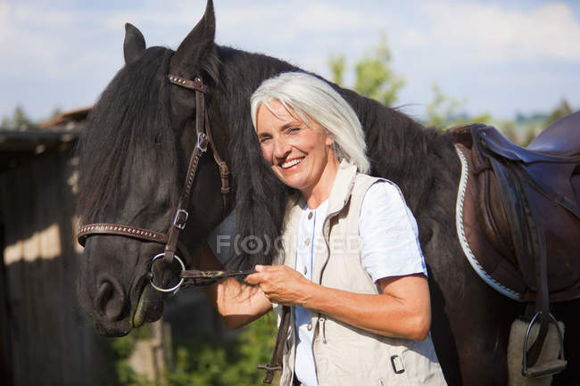 Mature woman hugging horse — Stock Photo