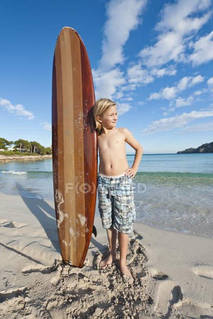 Мальчик с стоя для серфинга на пляже — стоковое фото