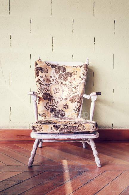 Закрыть вверх старых кресло против стены — стоковое фото
