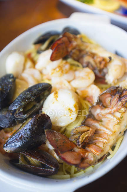 Seafood dish with lobster, mussels, scallops and pasta on plate — Stock Photo