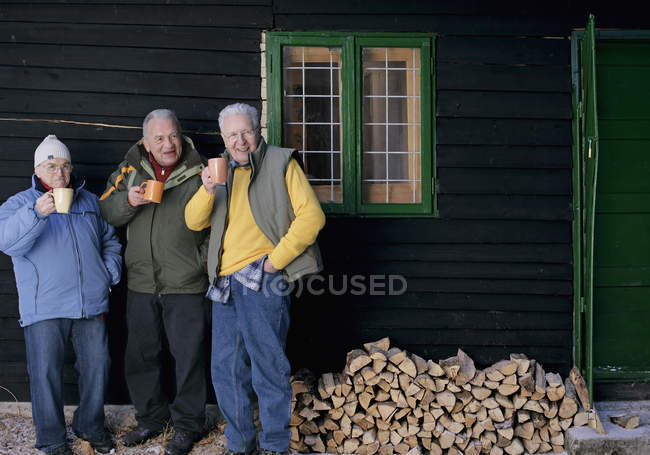 Senior men standing in front of log cabin with cups — Stock Photo