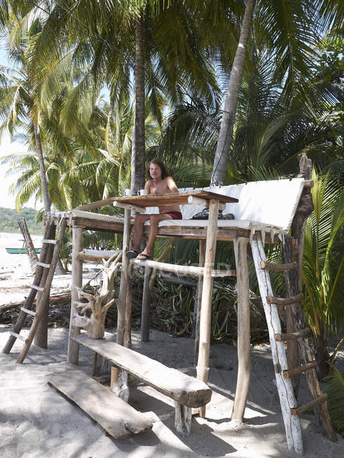 Центральної Америки, Коста-Ріка, людина, що сидить на дерев'яні високий присісти під пальмами — стокове фото