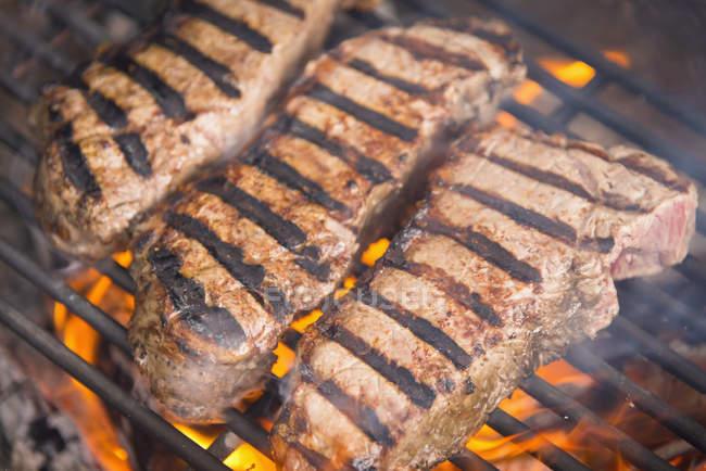 Strip Steak Grillen auf dem heißen Grill Feuer, Nahaufnahme — Stockfoto