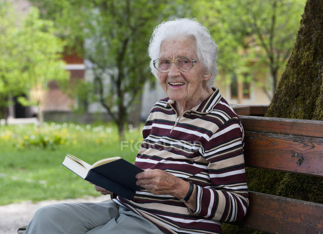 Старшая женщина сидит на скамейке и читает книгу — стоковое фото