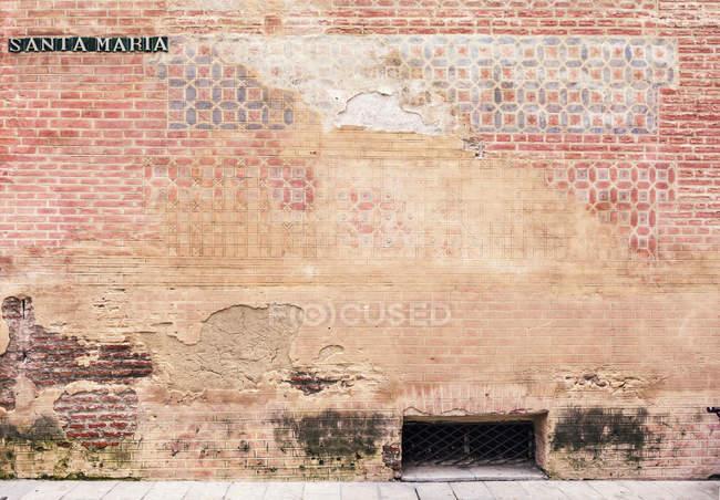 Spain, Malaga, Brick wall and Santa Maria street, close up — Stock Photo
