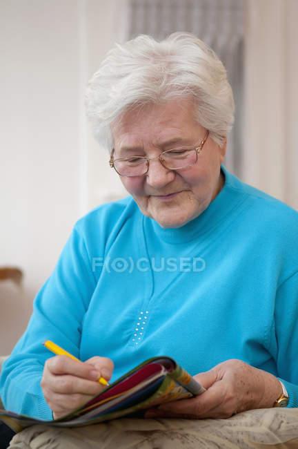 Senior woman doing crossword, smiling — Stock Photo