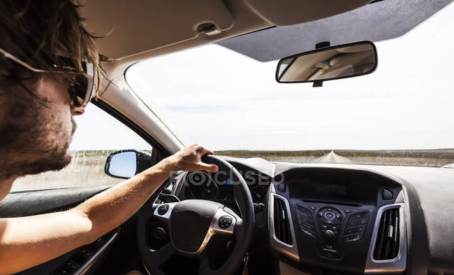 Young man driving car on road — Stock Photo