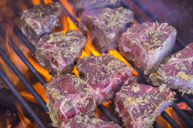 Lamb chop steaks grilling on barbecue — Stock Photo