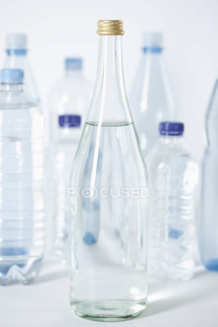 Glass bottles and plastic bottles, close up — Stock Photo