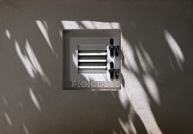 Closed window with shadow on built structure — Stock Photo
