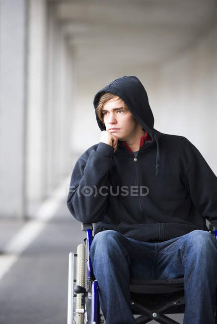 Young man sitting on wheelchair at subway — Stock Photo