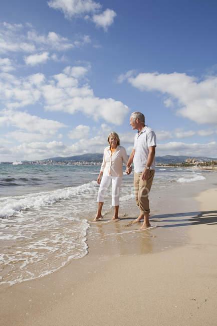 Старшая пара на пляже, улыбается — стоковое фото