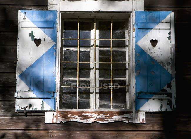 Finestra chiusa con griglia in casa di legno — Foto stock