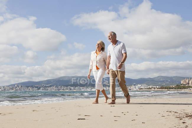Casal sênior, caminhando ao longo da praia, sorrindo — Fotografia de Stock