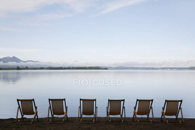 Germany, Bavaria, Chiemsee, Row of folded chairs by lake — Stock Photo