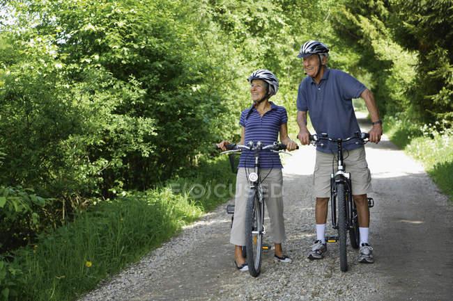 Casal sênior com bicicletas, sorrindo — Fotografia de Stock