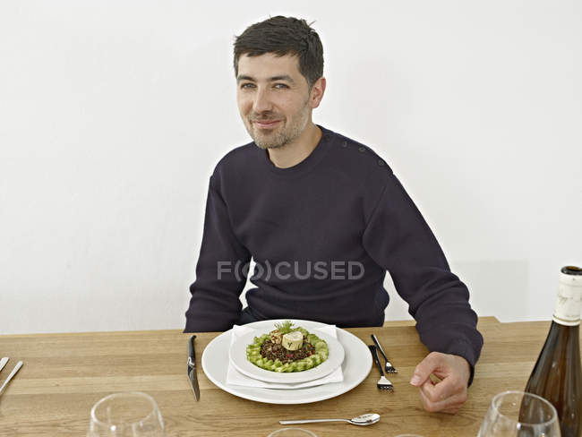 Mid adult man having dinner in kitchen, smiling, portrait — Stock Photo