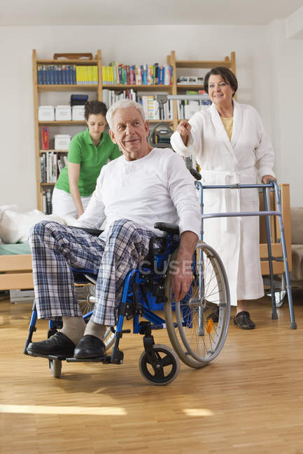 Senior man sitting on wheelchair, senior woman with walking frame — Stock Photo