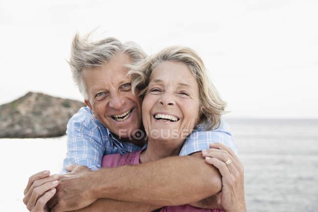 Casal sênior abraçando no porto, sorrindo — Fotografia de Stock