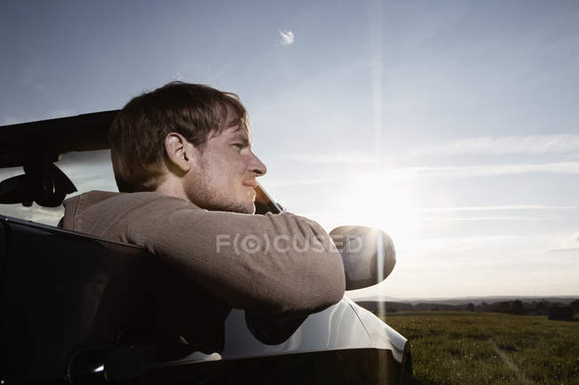 Man in car at sunset — Stock Photo