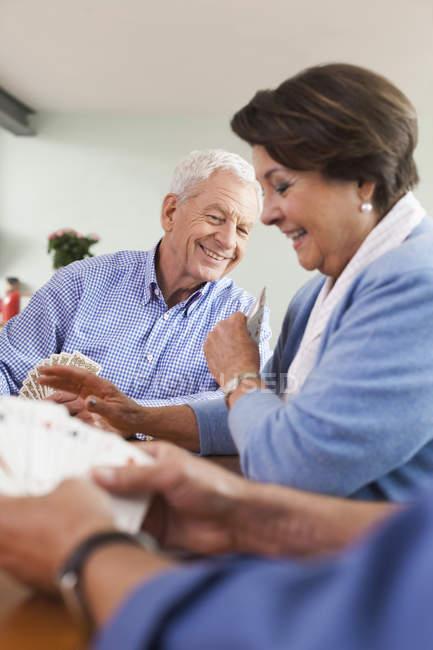 Senioren Herren und Spielkarten, lächelnde Frau — Stockfoto