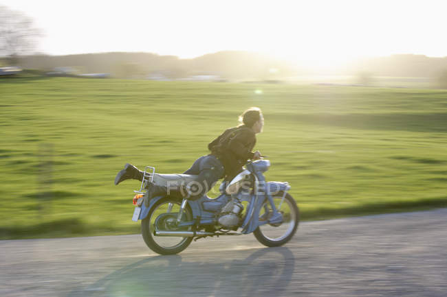 Mature woman riding old moped of 1960s — Stock Photo
