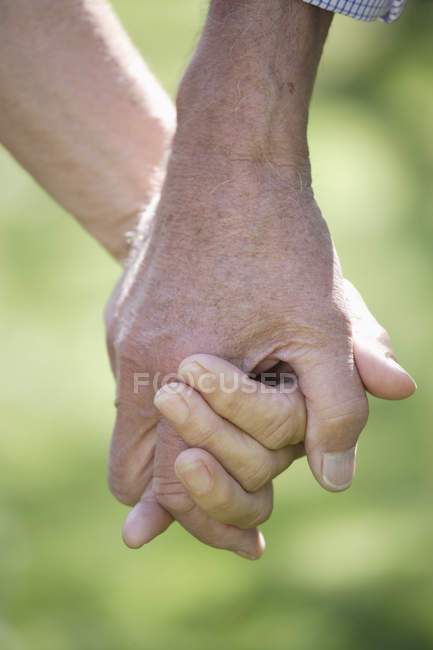 Senior couple holding hands, close up — Stock Photo