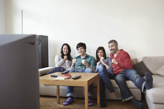 Men and women watching TV at home — Stock Photo