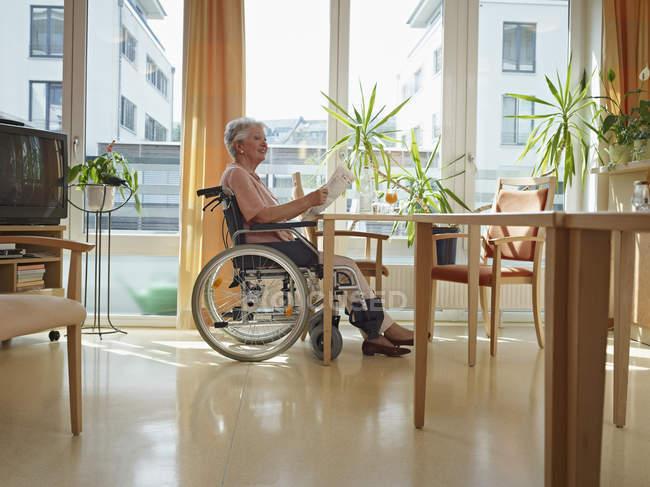 Senior woman reading newspaper in nursing home — Stock Photo